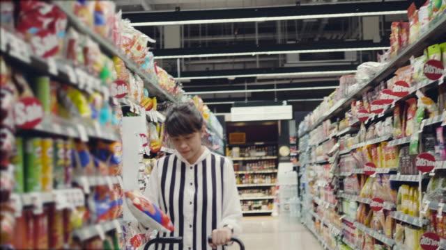 stockvideo's en b-roll-footage met jonge vrouw kiest voor levensmiddelen in de winkel - menselijke rug