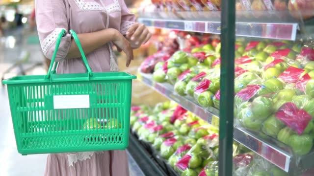 vídeos de stock, filmes e b-roll de jovem mulher escolhe frutas e compras no supermercado - carrinho meio de transporte