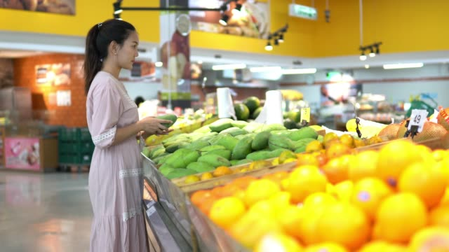 Young woman chooses Fruit and Shopping in supermarket