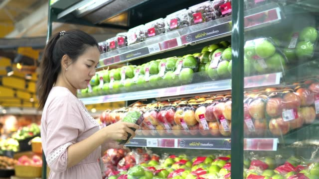 young woman chooses fruit and shopping in supermarket - freshness stock videos & royalty-free footage