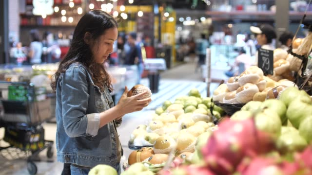 young woman chooses fruit and shopping in supermarket - market stock videos & royalty-free footage