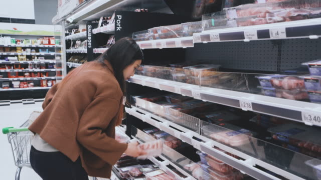 young woman chooses meat shopping in supermarket - europe stock videos & royalty-free footage