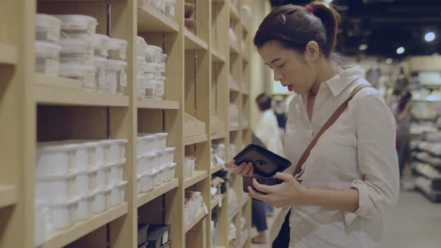 young woman chooses plastic box in shopping mall - plastic container stock videos & royalty-free footage