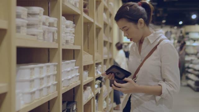 vídeos de stock, filmes e b-roll de jovem mulher escolhe caixa plástica em shopping center - contéiner de plástico