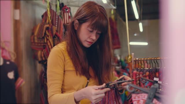 stockvideo's en b-roll-footage met jonge vrouw kiest rok in rommelmarkt. - rommelmarkt