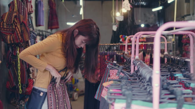 Young woman chooses skirt in flea market.