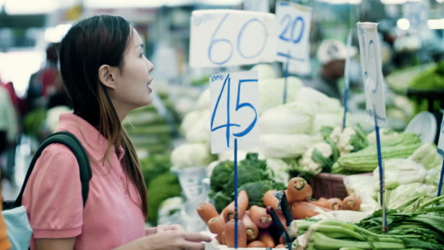 Young woman chooses vegetables at grocery section of supermarket
