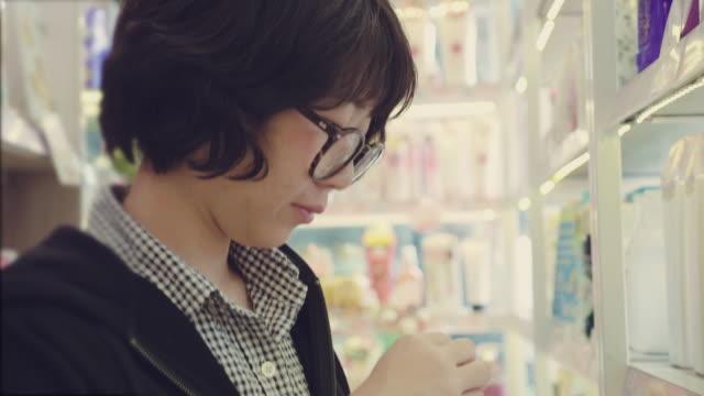 junge frau, die wahl eines lippenstifts auf beauty shop. - shampoo stock-videos und b-roll-filmmaterial