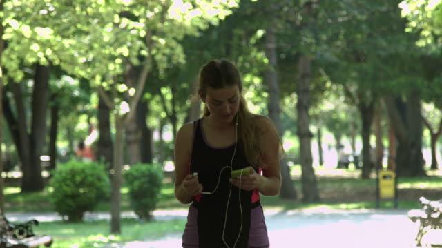 vidéos et rushes de jeune femme choisissant une musique sur le téléphone - joggeuse
