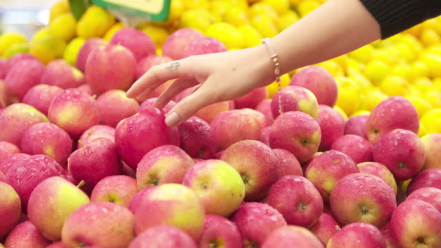 Young woman choosing an apple in a supermarket