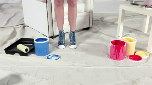 vídeos de stock e filmes b-roll de young woman choosing blue paint can - pano de protecção