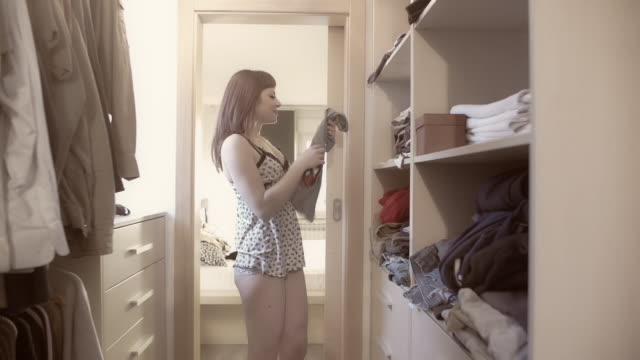 vidéos et rushes de young woman choosing clothes in a walk-in wardrobe - rangement