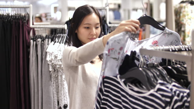young woman choosing clothes on rack in showroom - matching outfits stock videos & royalty-free footage