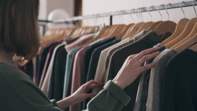 young woman choosing clothes on rack - boutique stock videos & royalty-free footage
