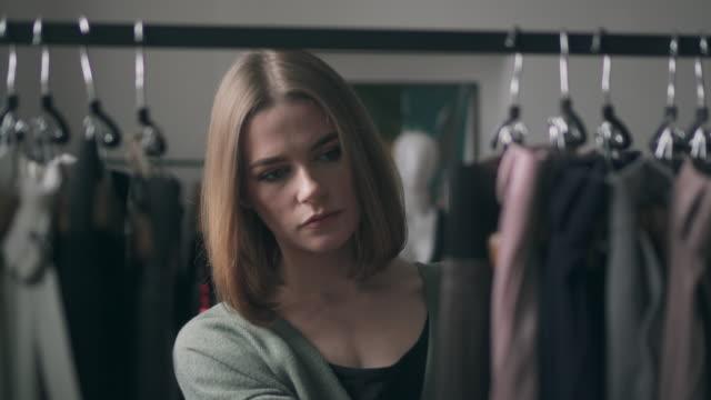 vídeos de stock, filmes e b-roll de jovem mulher escolhendo roupas no cesto - escolhendo