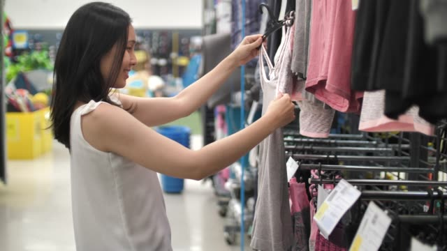 young woman choosing coat on rack in showroom - garment stock videos & royalty-free footage