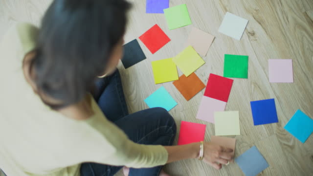 stockvideo's en b-roll-footage met ms young woman choosing colour swatches for her home. - kiezen