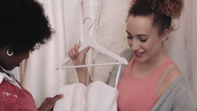 young woman choosing dress for wedding with her mother - dress stock videos and b-roll footage