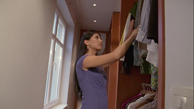 ms, young woman choosing dresses from cupboard, brussels, belgium - cupboard stock videos & royalty-free footage