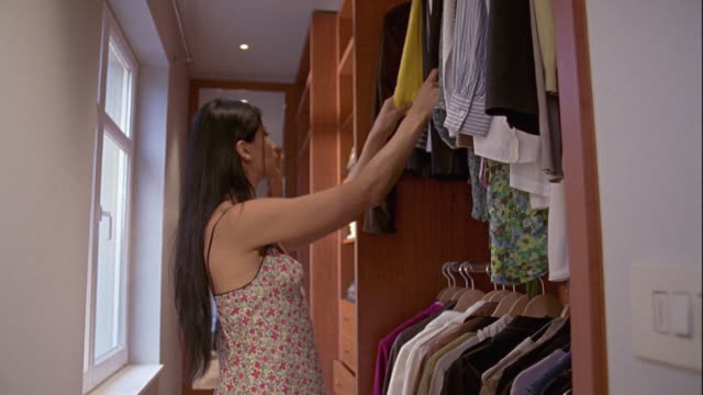 ms, focusing, young woman choosing dresses from cupboard, brussels, belgium - kamisol stock-videos und b-roll-filmmaterial