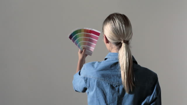Young woman choosing paint color from swatches