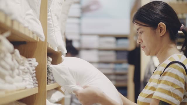 young woman choosing pillow in furniture store - bedclothes stock videos & royalty-free footage