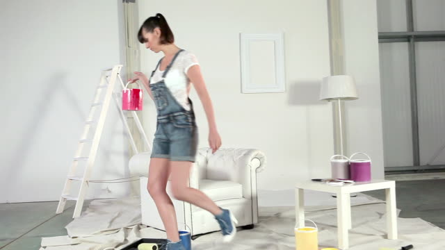 vídeos de stock e filmes b-roll de young woman choosing red paint can - pano de protecção