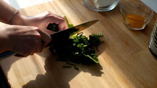 vídeos y material grabado en eventos de stock de mujer joven para picar espinacas verdes frescas en la cocina en el tablero de corte - haz de luz
