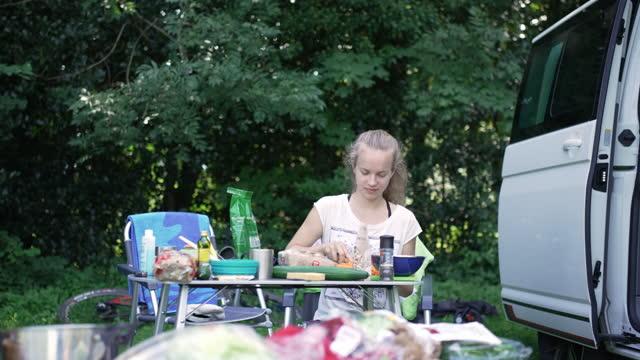 vídeos y material grabado en eventos de stock de mujer joven cortando verduras en un picnic - menos de diez segundos