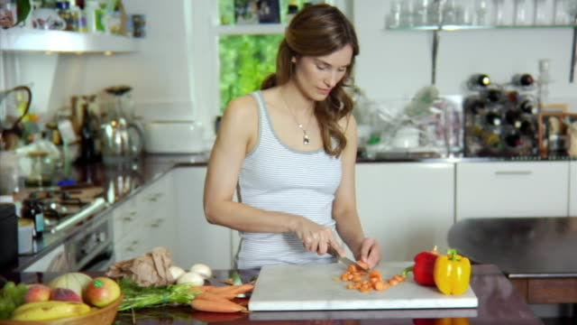SLO MO CU ZO MS Young woman chopping vegetables in kitchen / London, United Kingdom