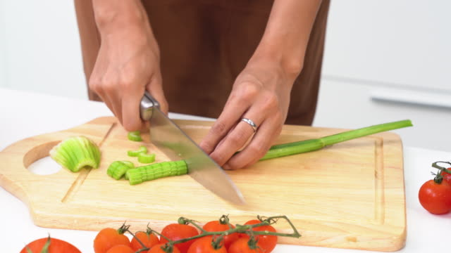 young woman chopping vegetables in the kitchen - kitchenware department stock videos and b-roll footage