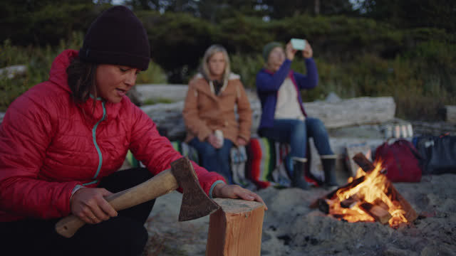 young woman chops firewood on the beach at sunset as friends sit by the campfire. - キャンプする点の映像素材/bロール