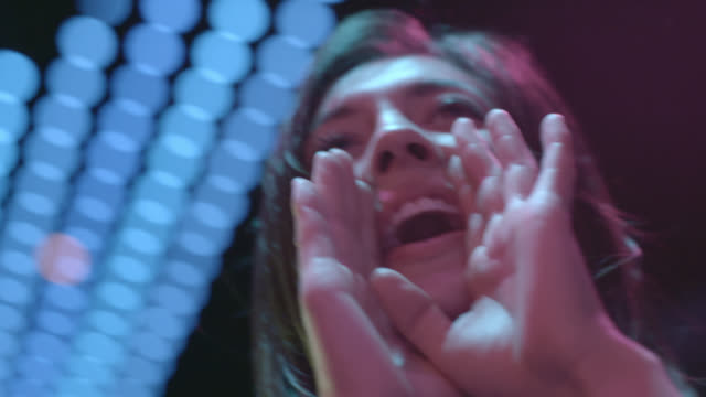 Young woman claps and cheers under neon lights in nightclub