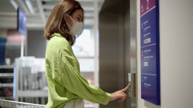 vídeos de stock e filmes b-roll de young woman cleaning and disinfect virus before using lift - elevador