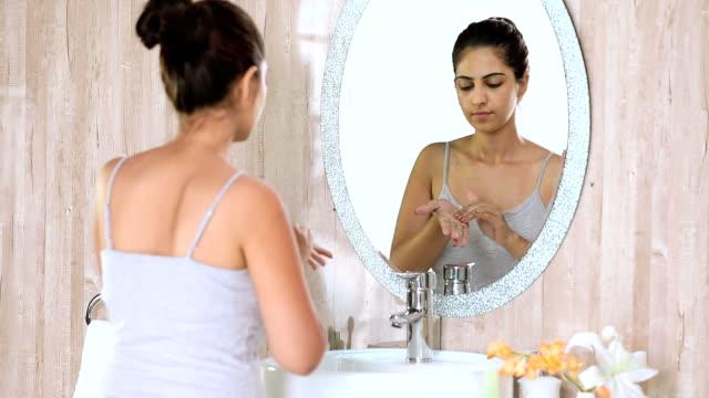vídeos de stock, filmes e b-roll de young woman cleaning face in bathroom, delhi, india - coque cabelo para cima