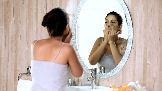 Young woman cleaning face in bathroom, Delhi, India