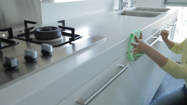 vídeos de stock e filmes b-roll de ms pan young woman cleaning kitchen counter cabinets / china - limpar