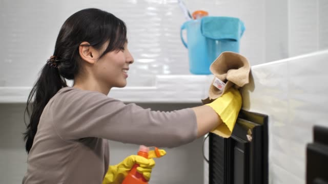 young woman cleaning the kitchen with spray - stereotypical homemaker stock videos & royalty-free footage