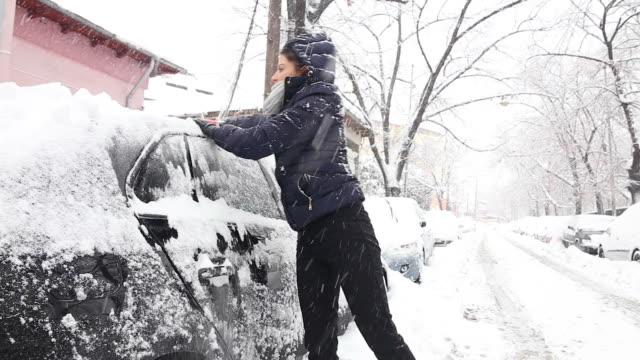Junge Frau Reinigung der Schnee von einem Auto.