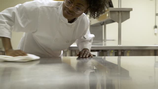 Young woman cleaning work surface in catering college.