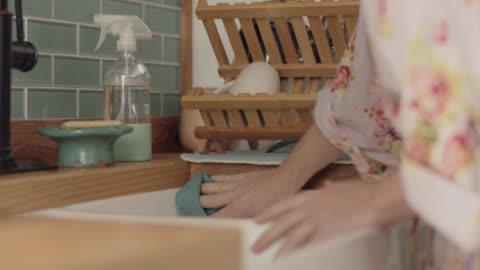 vídeos y material grabado en eventos de stock de cu young woman cleans sink with cloth, rinses cloth with water from faucet - clean