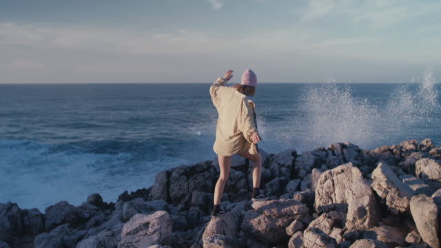 vídeos de stock e filmes b-roll de young woman climbing on sea cliffs on water's edge looking at waves - equilíbrio