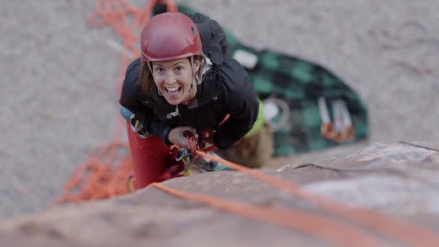 stockvideo's en b-roll-footage met slo mo. young woman climbing rock face looks up at camera and smiles. - rotsklimmen