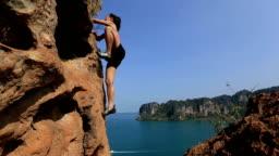 young woman climbing rock seaside
