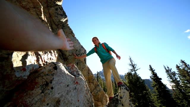 Giovane donna arrampicata su rocce, scrivete a mano