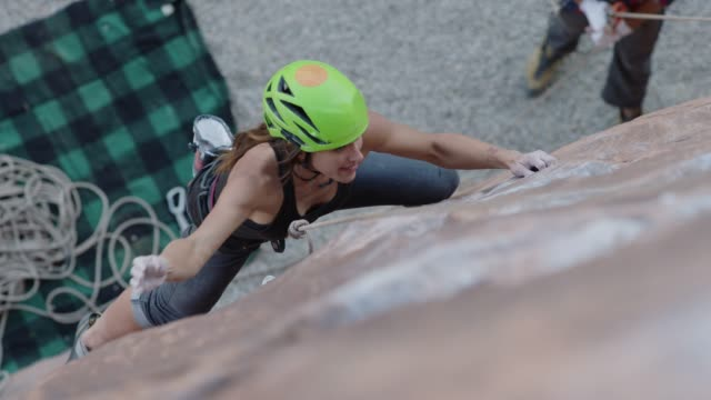 stockvideo's en b-roll-footage met slo mo. young woman climbing steep rock face turns to look down. - boulder rock