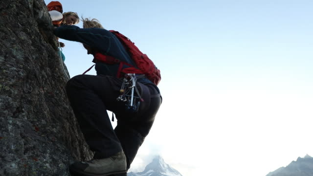 young woman climbs as mother belays, matterhorn distant - european alps stock videos & royalty-free footage