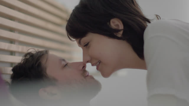 Young woman climbs into bed to give man a good morning kiss