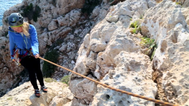 young woman climbs on rope above sea - climbing rope stock videos & royalty-free footage