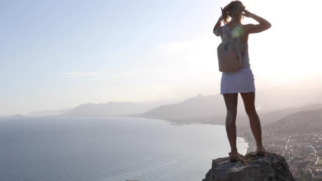 vídeos de stock, filmes e b-roll de a mulher nova escala na cimeira da rocha no nascer do sol - mãos estendidas